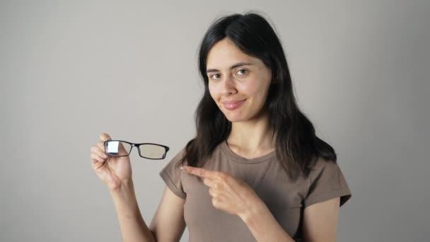 Mädchen mit Brille isoliert auf grauem Wandhintergrund.