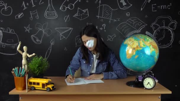 Portrét krásné školačka student, přemýšlet o volbě povolání, na pozadí černé desce s obrázkem zeměkoule. Koncepce: myšlenky, škola, univerzita, vzdělání.