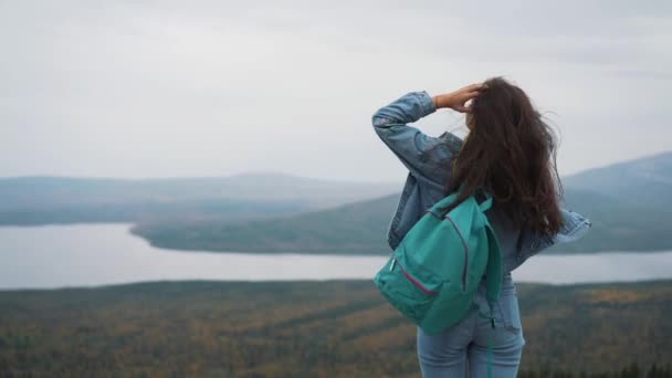 Attractive woman standing on a mountain peak with her long hair blowing in the wind smiling and trying to keep her hair off her face with her hand