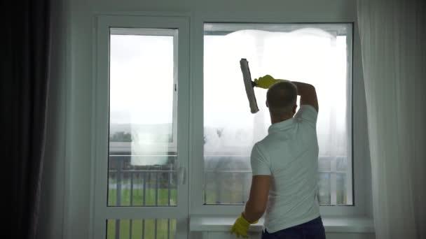 Muž z úklidové firmy myje okna