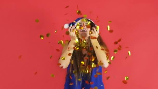 Ženy slaví Nový rok na červeném pozadí s zlaté konfety