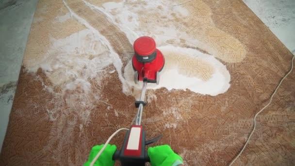 Možnost profesionálního čištění koberců. Člověk čistí špinavé koberce. Čistí se pěna po čištění. Čištění s elektrická pračka koberců