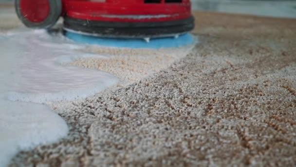 professionelle Teppichreinigung. Mann reinigt schmutzigen Teppich. reinigt den Schaum nach der Reinigung. Teppichreinigung mit elektrischem Schrubber