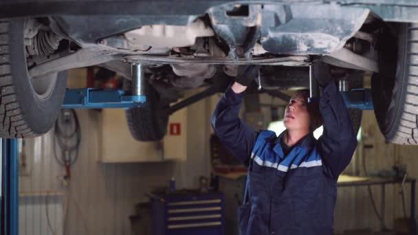 auto servis, opravy, údržbu a lidé koncept - mechanik muž s klíčem a lampa pracuje v dílně.