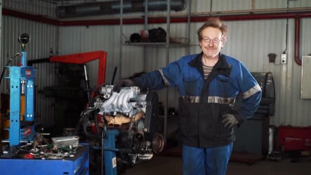 Portré fiatal gyönyörű autószerelő a autó-workshop, a háttérben a törött autó. Koncepció: gép javítás, hiba felderítése, szakosodott javítása, karbantartása.