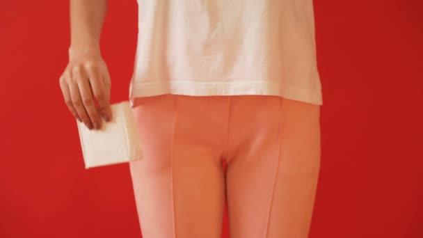 Das Konzept der Menstruation, Eisprung bei Mädchen. Mädchen auf einem roten Hintergrund hält einen Tampon, Dichtung