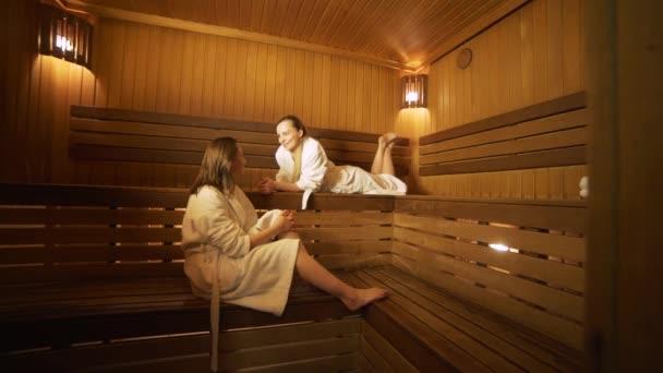 zwei glückliche Frauen im Gespräch miteinander in einer Sauna