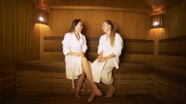 Dvě šťastné ženy mluvit k sobě navzájem v sauně