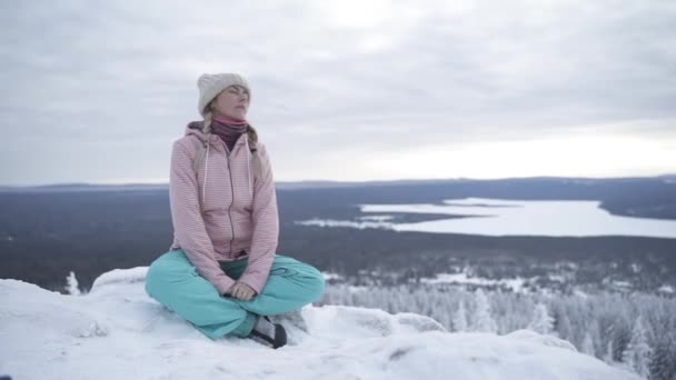 Girl sitting on the snowy stones and relaxing
