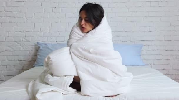 Erkältungszeit, laufende Nase. Krankes Mädchen im Bett niest in Taschentuch im Schlafzimmer