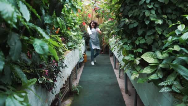 A beautiful girl in an apron dancing in a greenhouse. Florist happy, dancing and laughing.