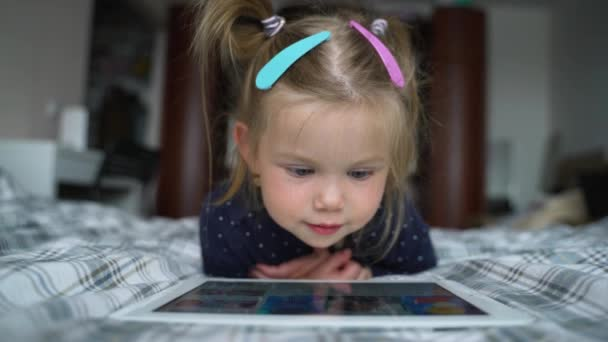 Curious cute preschool kid girl using digital tablet technology device lying on carpet floor alone. Small child hold pad computer surfing internet play game at home. Children tech addiction concept.