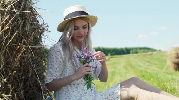 Krásná žena v bílých šatech a klobouku, sedí v kupce sena a sbírá květiny na poli