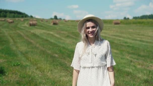Portrét dívky v bílých šatech a klobouku stojí v poli a usmívá se do kamery