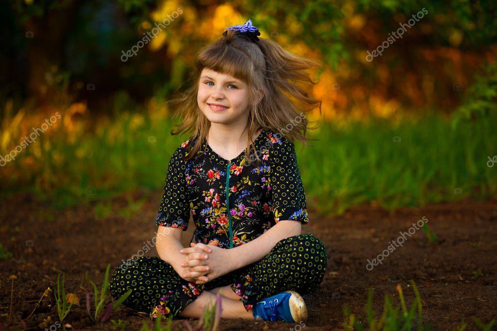Beautiful smiling girl walking in park at sunset