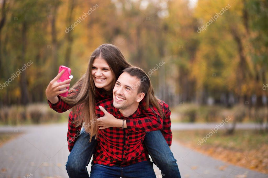 Love couple dressed in identical red shirts hugging on street in autumn park, walking outdoors.