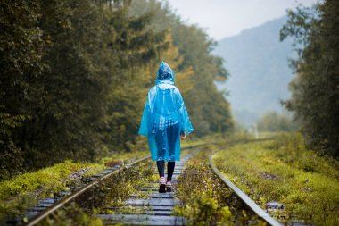 Girl traveller wearing blue jacket and go by forest railway. Autumn and raining season with dark green tones while girl in blue rain jacket walks in forest, fog, rain and clouds
