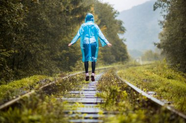 Girl traveller wearing blue jacket and go by forest railway. Autumn and raining season with dark green tones while girl in blue rain jacket walks in forest, fog