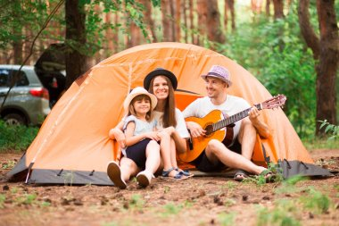 Happy family camping in forest, playing guitar and singing song together in front of tent. Concept of trekking, family.