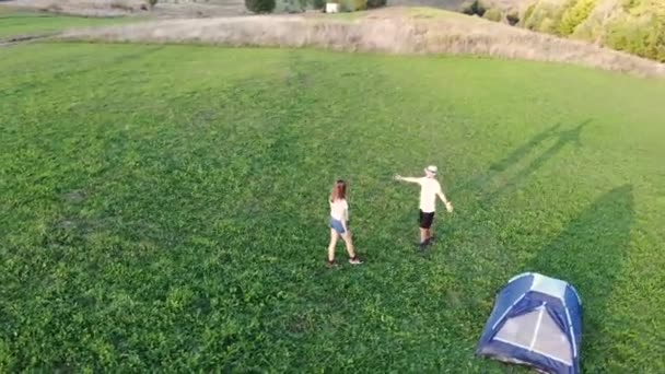 Aerial view drone flying over young pair of travellers hugs and relaxing with tent enjoying view of mountain. Active lifestyle