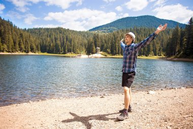 Free man with open arms near mountains lake. success. Travel and Freedom concept. Good life.