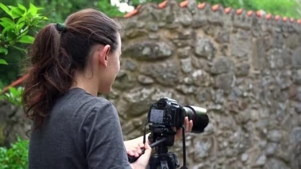 Ein junges Mädchen, ein Fotograf, macht in einem Waldgebiet Fotos von der schönen Natur. Nahaufnahme.