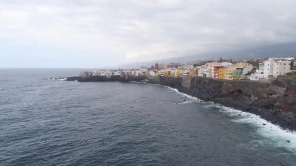 TENERIFE, PUNTA BRAVA, SPAIN - MAY, 18, 2018: Aerial view of rocky coast of Atlantic ocean and colorful houses on waterfront. Drone shot from above in 4K