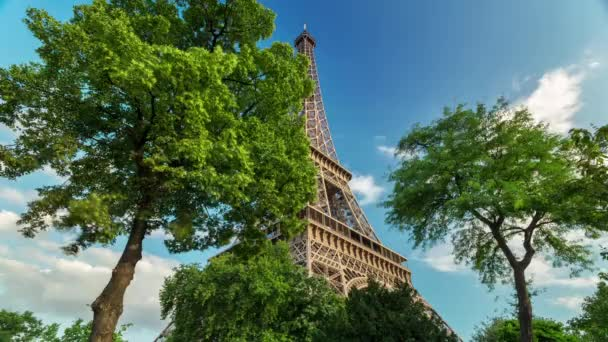PARIS, FRANCE - JUNE 19, 2018: Eiffel Tower day timelapse. Sunny day with clouds. Green trees. 4K shot