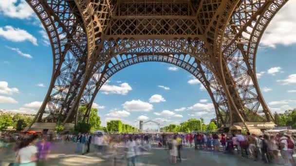 PARIS, FRANCE - JUNE 19, 2018: Eiffel Tower day timelapse with people walking around. Sunny day with clouds. 4K shot