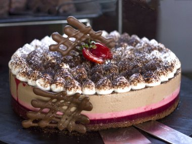 Cheesecake pie with raspberries, decorated with fresh strawberries, on black background
