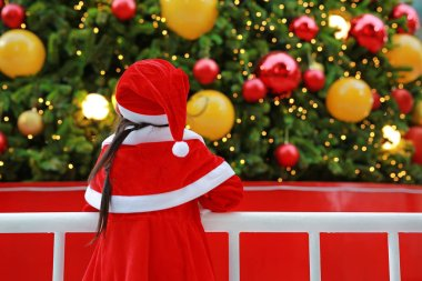 Back view little child girl in Santa costume looking Christmas tree. Christmas winter holiday concept.