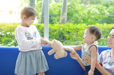 Asian sister scrambling teddy bear with her little brother and mom take care her children.