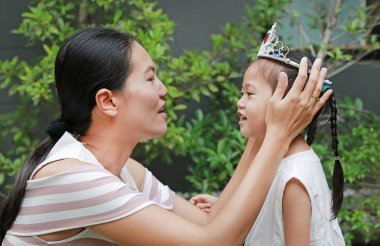 Mother wearing crown on head of little girl and a white dress