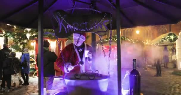 Riga, Latvia - December 18, 2017: Man In A Festive Christmas Costume Cooking Mulled Wine On Traditional Christmas Market On Dome Square.