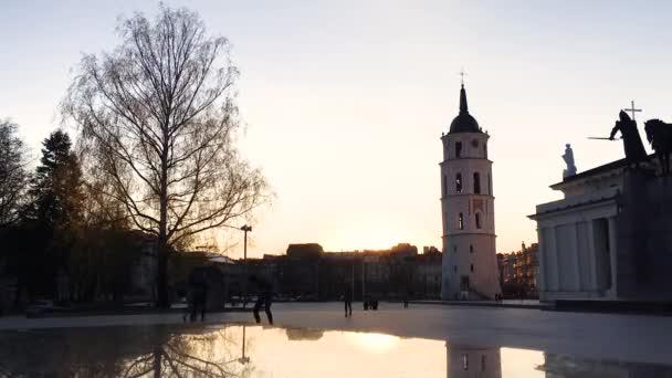 Vilnius, Litva. Náměstí poblíž Katedrála Basilica rákosem a St. Vladislav s zvonice v jarní slunce slunečný večer. Time Lapse Time-lapse Timelapse