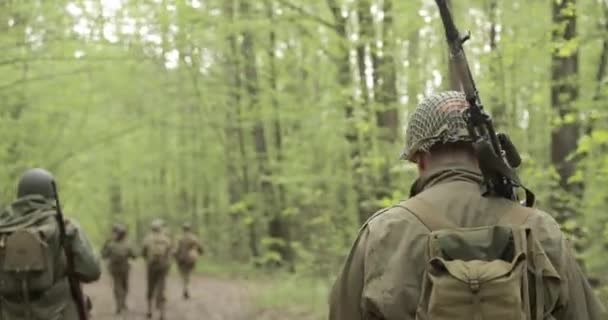 American Soldiers Of USA Infantry Of World War II Marching Walking Along  Forest Road In Summer Day  Group of Soldiers Marching In Forest