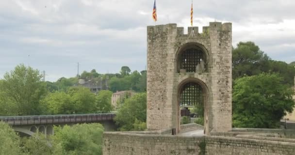 Besalu, Girona, Catalonia, Spain. Famous Landmark Old Medieval Romanesque Besalu Bridge Over The Fluvia River In Cloudy Summer Day