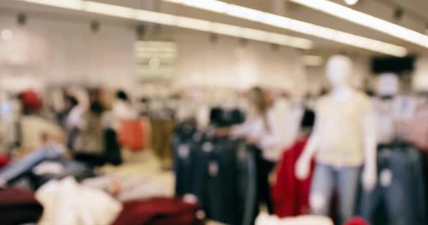 Blured Bokeh pohled na oblečení na policích a zavěšení v obchodě Nákupní centrum