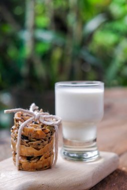 Stack of cookies with a glass of milk on wooden board with copy space