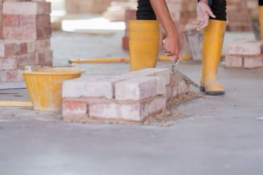 College students  working brick wall construction in bricklaying workshop