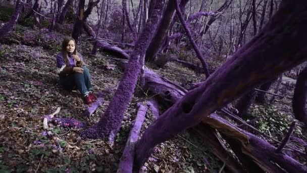 Violet fairytale forest. Beautiful girl in a lilac jacket sits in a fabulous lilac forest and looks at the flower in her hand.