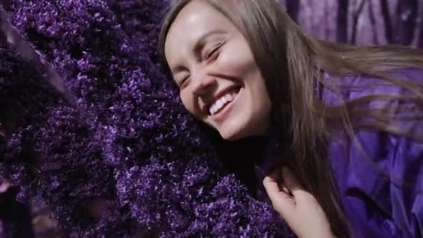 Violet fairytale forest. Happy girl in a lilac jacket touches the soft thick purple moss on a tree and smiles. Fantasy, unreal, fairytale atmosphere