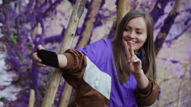 Violet fairytale forest. Happy girl in a purple olympium makes a peace-selfie on the background of the moss-covered trees in a foggy boxwood forest. Fantasy, unreal, fairytale atmosphere