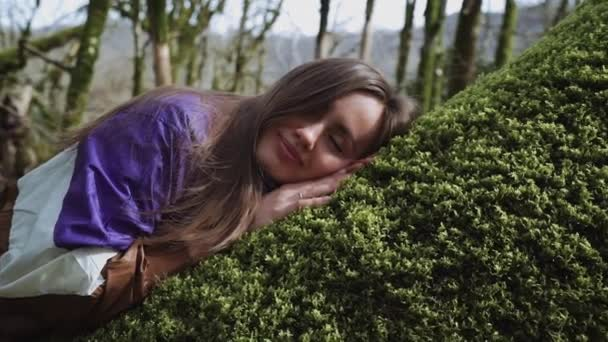 Beautiful girl in purple jacket sleeps on green moss in the middle of the forest