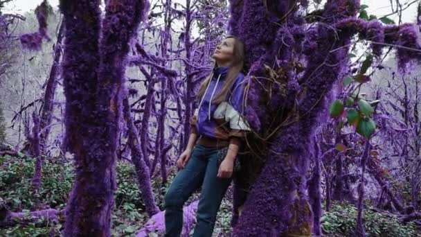Violet fairytale forest. Girl is leaning against a moss-covered tree in a mysterious purple forest, zooming out. Fantasy, unreal, fairytale atmosphere