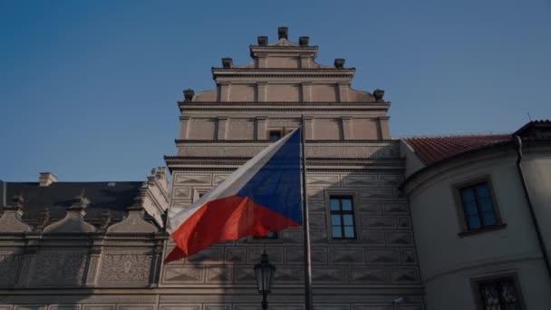 Vlajka České republiky mávaje větrem, v pozadí je vládní budova s modrou oblohou a sluncem