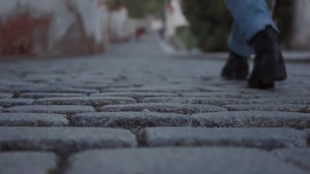 Legs of a woman in black boots and jeans walking along cobbled streets of European cities in close up
