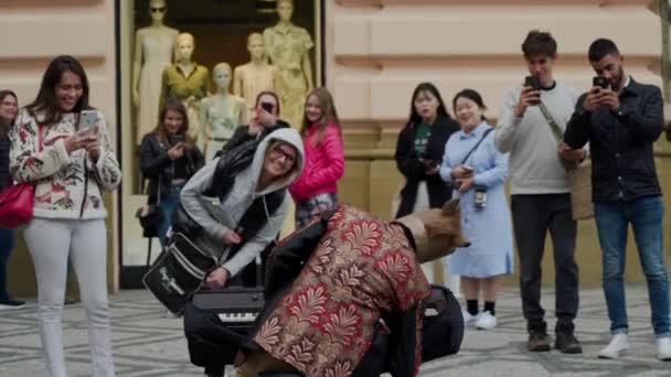Prag, 16. Mai 2019: Touristen fotografieren vor der Kamera, schauen mit Interesse auf fröhlichen Straßenmusiker im Pferdekostüm hinter Synthesizer, Rückansicht
