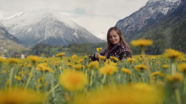 Young beautiful caucasian woman in patterned coat sitting in a blooming field picks flowers and collects a bouquet of yellow dandelions. Spring summer day