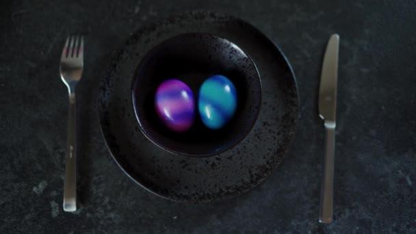 Horní pohled na dvě barevná velikonoční vajíčka na černé desce na tmavém pozadí. Ženská ruka bere obě vejce. Talíř zůstává prázdný. Zavřít
